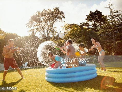 Father Aims a Water Gun at Children Throwing Water in a Paddling Pool : Foto de stock
