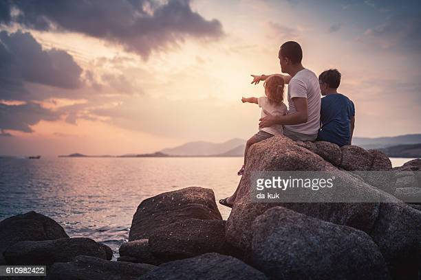 Father anв his children watching the sunset over sea