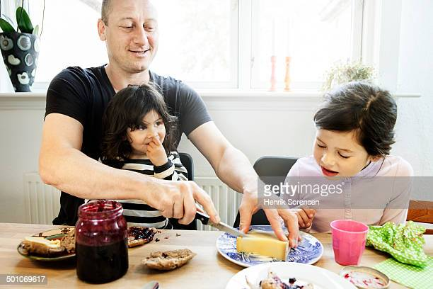Father and 2 daughters eating breakfast