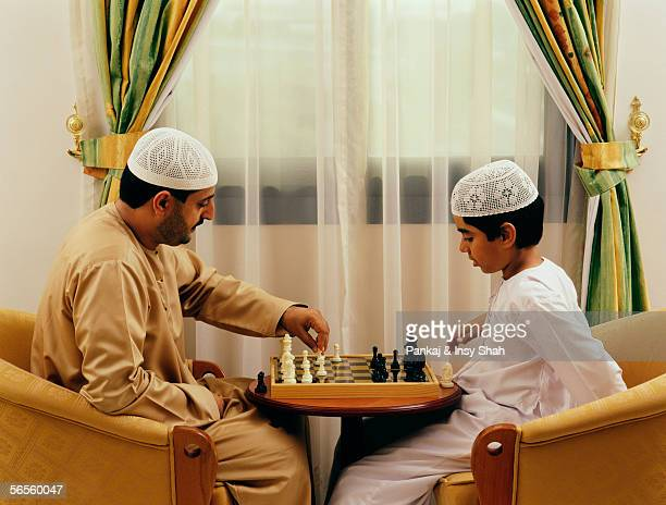 A father and a son playing chess at their residence.