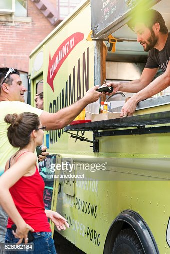 Father and adult daughter paying lunch from food truck in city street. : Stock Photo