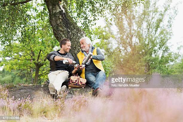 Father and adult son drinking coffee from flask
