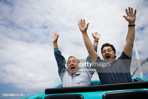 Father and adult son riding rollercoaster, hands in air