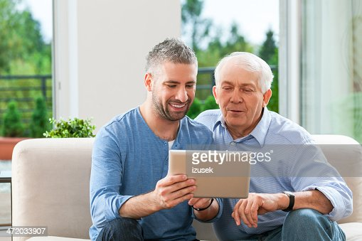 Father and adult son with digital tablet