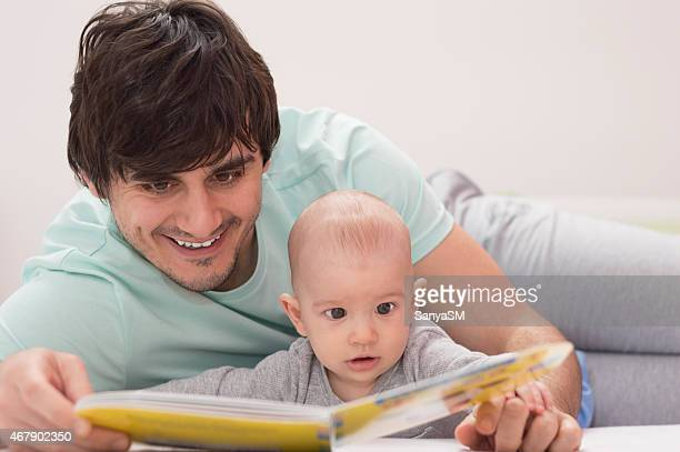 Father and baby are reading a book