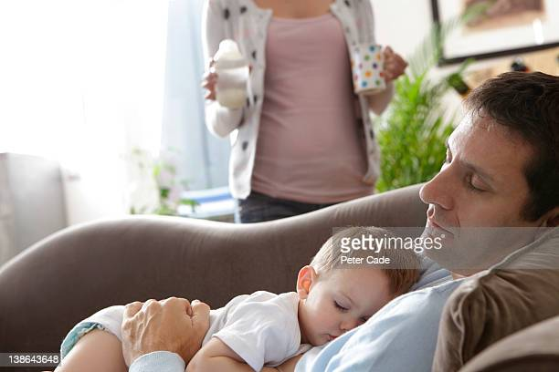 father and baby asleep on sofa