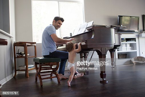 Father and baby boy playing on piano