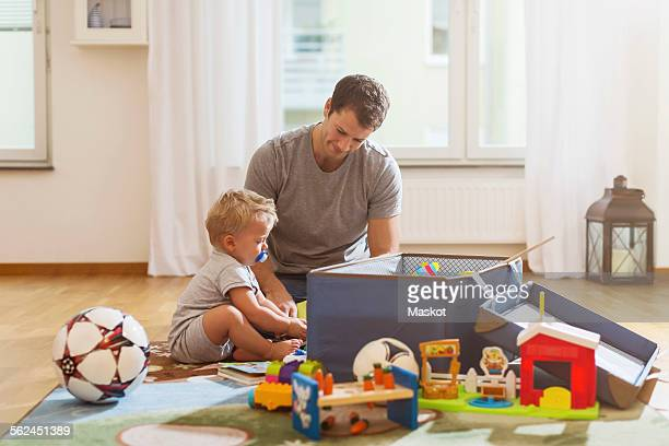 Father and baby boy playing with toys at home