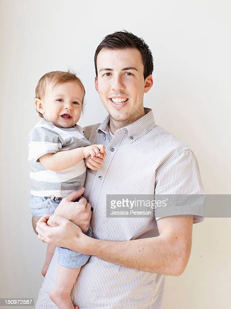 Father and baby boy (6-11 months) posing for portrait