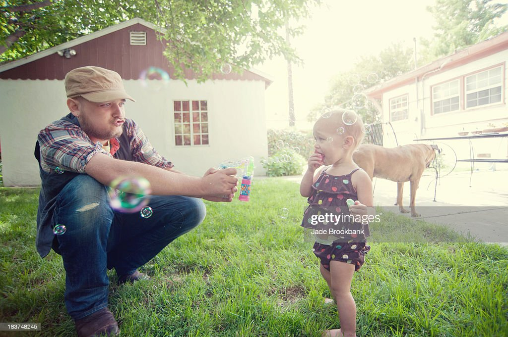 Father and baby daughter playing with bubbles in garden : Stock Photo