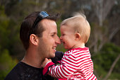 Father and baby daughter smiling while playing