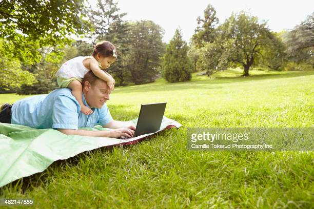 Father and baby girl using laptop in park