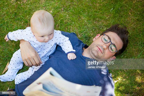 Father and baby lie on grass reading newspaper