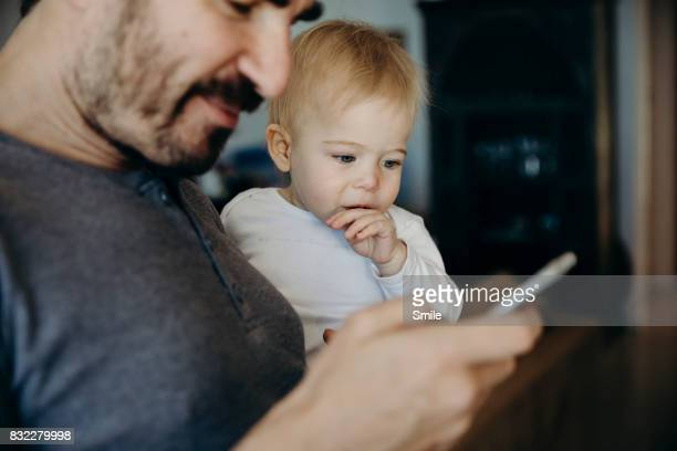 Father and baby looking at smart phone
