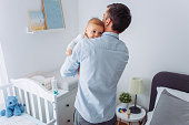 Father carrying baby son in bedroom, they share moment of love
