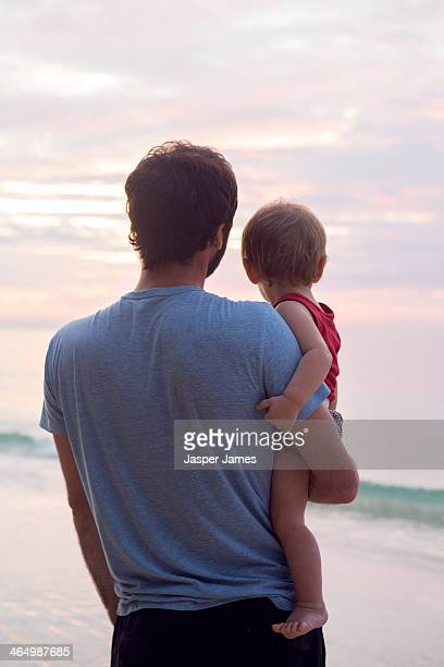 father and baby sun looking at sunrise at the beac