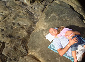 Father and child asleep on rock