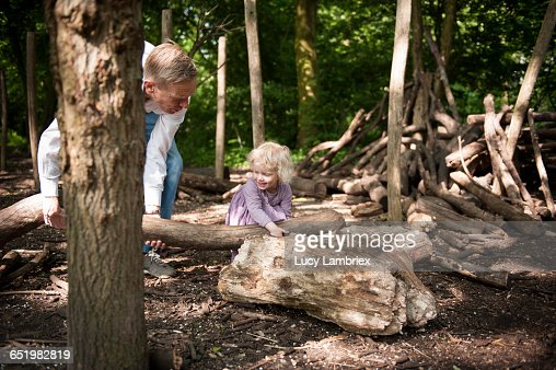 Father and child carrying a log : Stockfoto