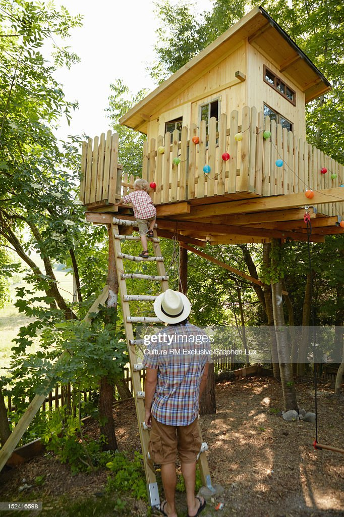Father and child climbing tree house : Stock Photo