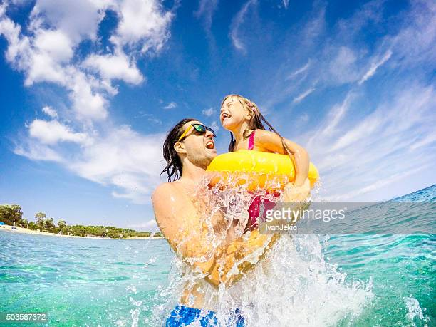 Father and child jumping and having fun together in sea