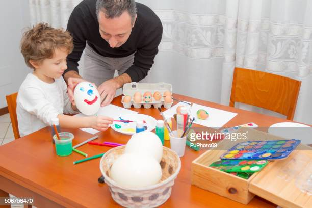 Father and child painting Easter eggs