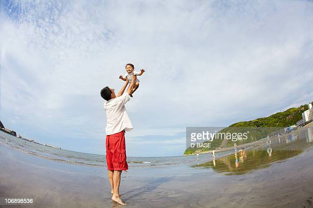 Father and child playing at beach.