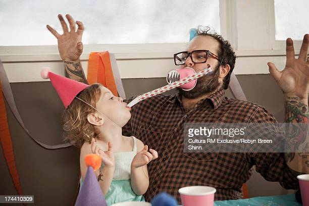 Father and child playing with party blower