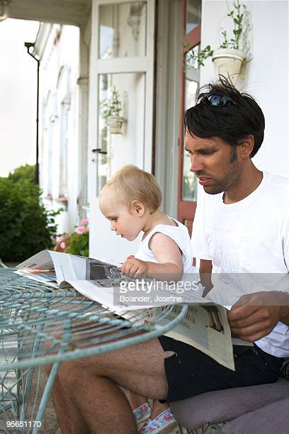 Father and child reading the newspaper, Sweden.