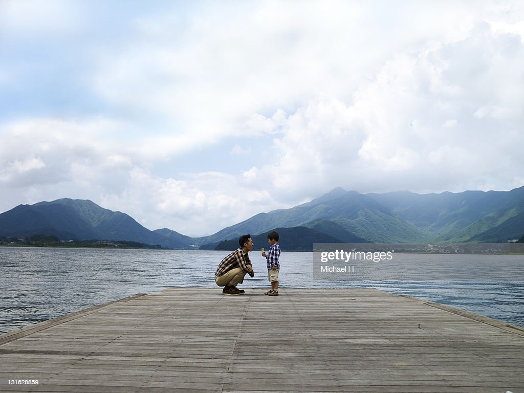 Father and child to talk on the pier : Stock Photo