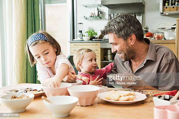 Father and children baking in kitchen