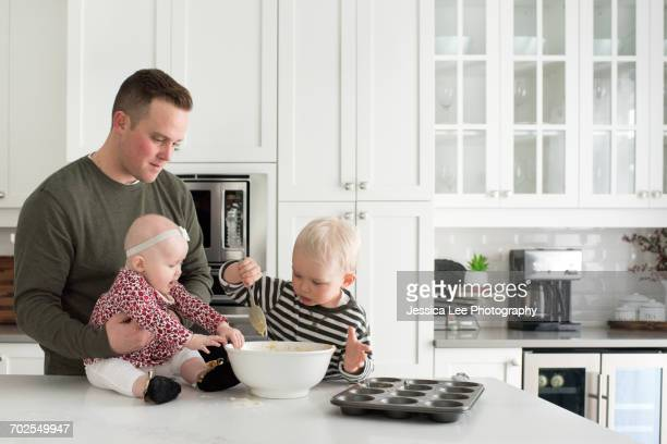 Father and children baking together, son putting mixture into baking tray