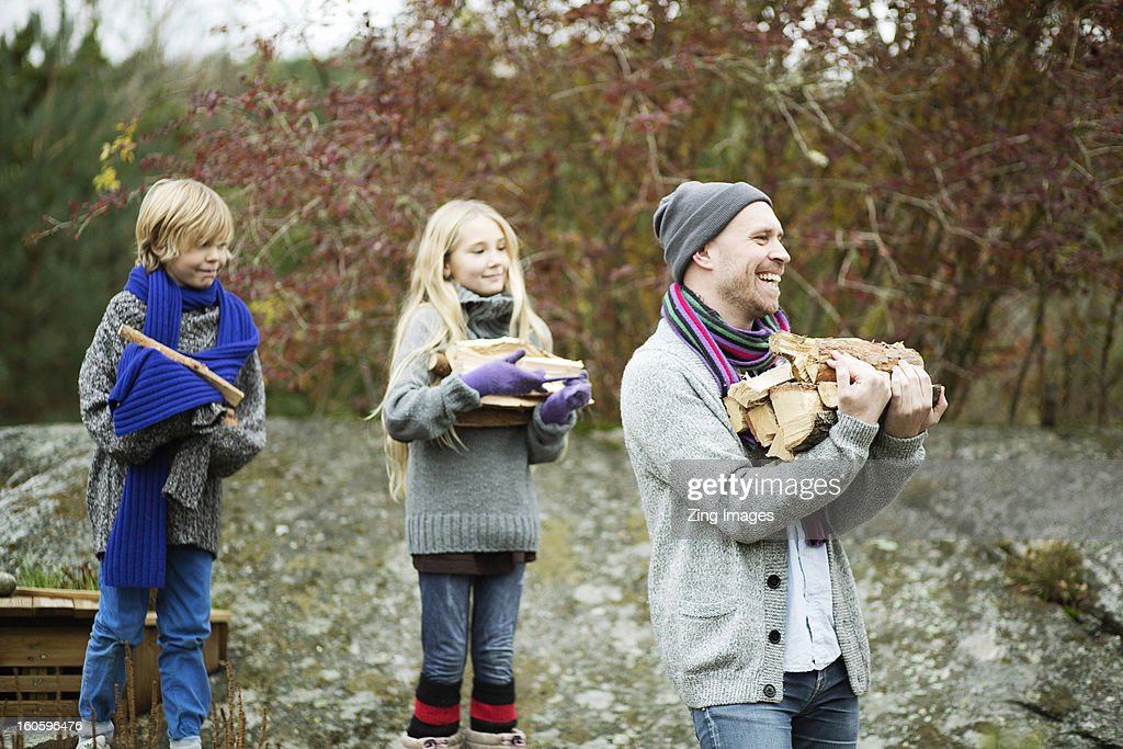 Father and children carrying logs : Stock Photo