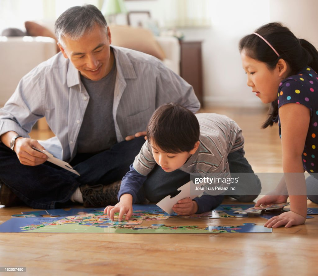 Father and children doing jigsaw puzzle together : Stock Photo