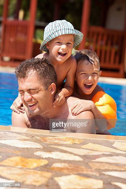 Father and children enjoying in the swimming pool