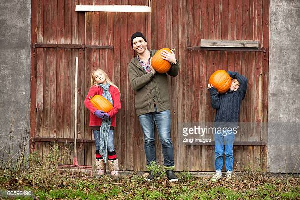 Father and children holding pumpkins