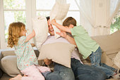 Father and children in pillow fight