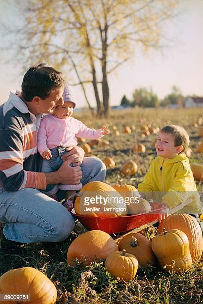 Father and children in pumpkin patch