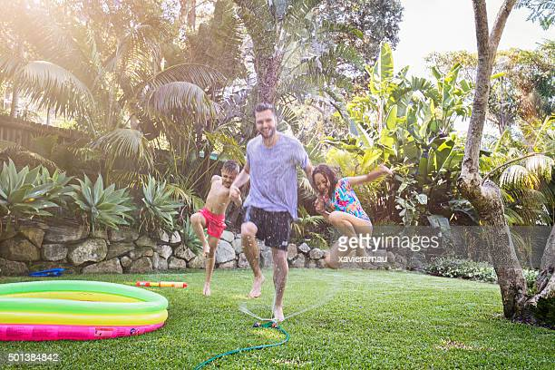Father and children jumping in sprinkler