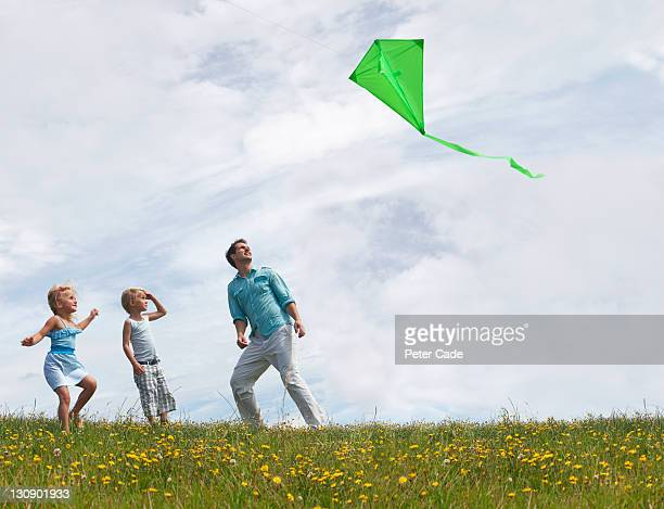 father and children looking up at green kite