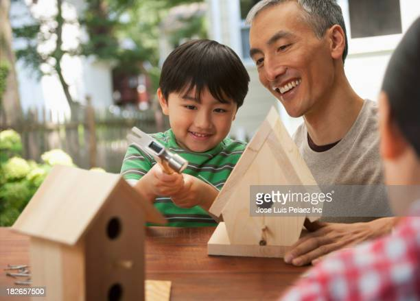 Father and children making birdhouses together