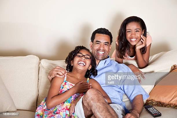 Vater und Kinder auf Sofa mit Fernbedienung