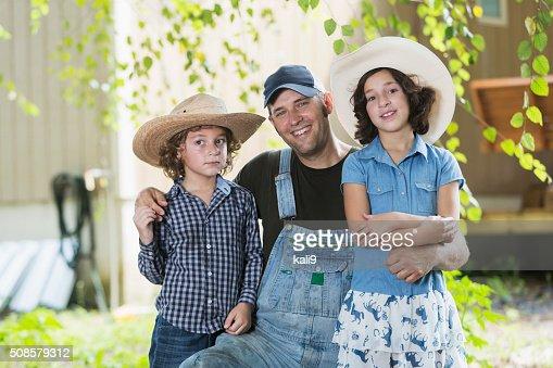 Père et les enfants à la ferme en famille, souriant à la caméra : Photo