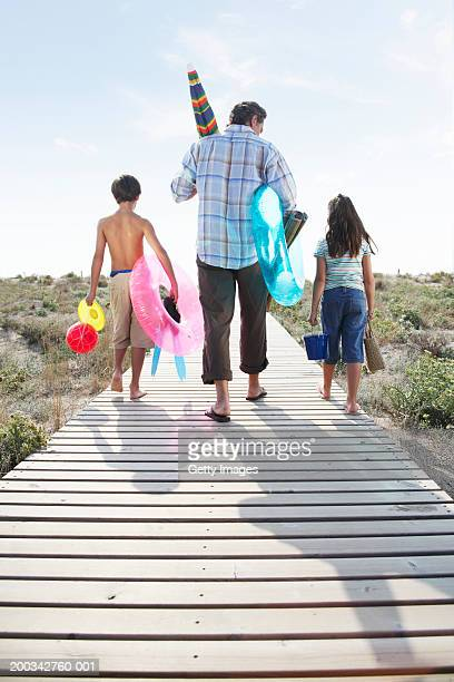 Father and children (7-9) on path carrying beach toys, rear view