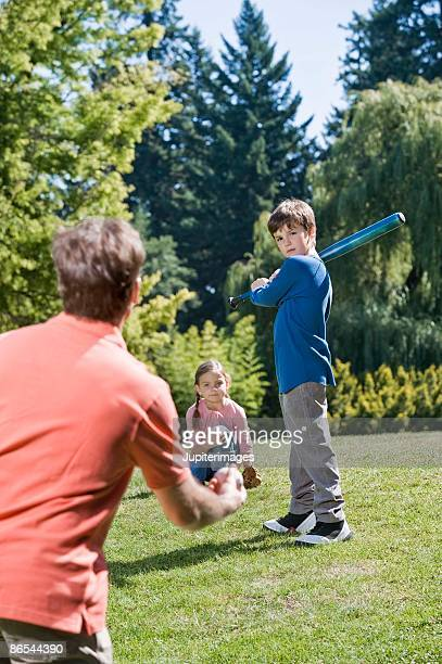 Father and children playing baseball