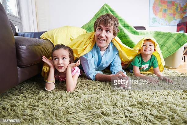 Father and children playing in blanket fort in living room