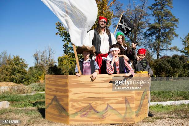 Father and children playing in pretend pirate ship
