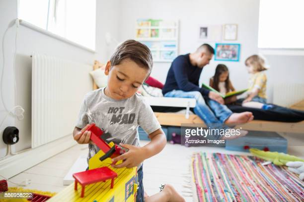 Father and children (2-3, 6-7) playing in room