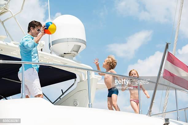 Vater und Kinder spielen mit Ball auf Yacht