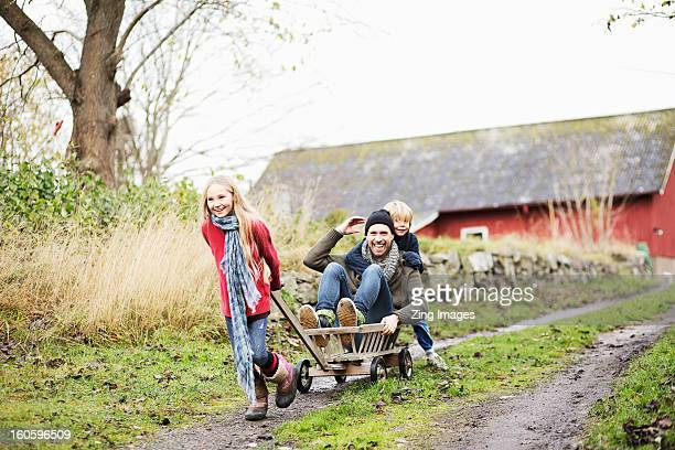 Father and children playing with go cart
