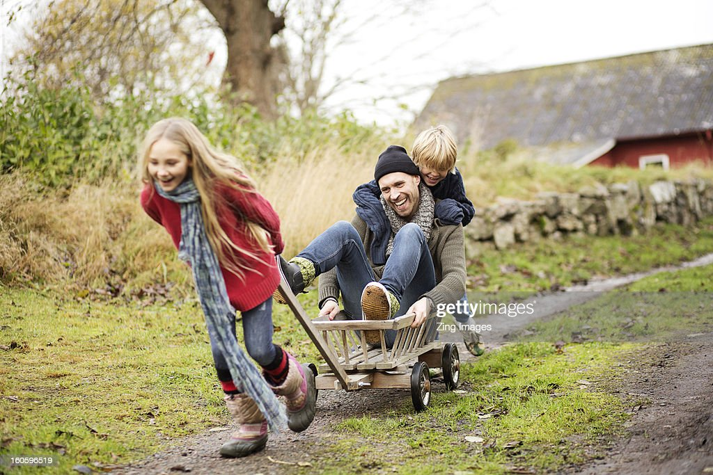 Father and children playing with go cart : Stock Photo